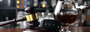 Picture of an alcoholic drink next to car key fob and gavel